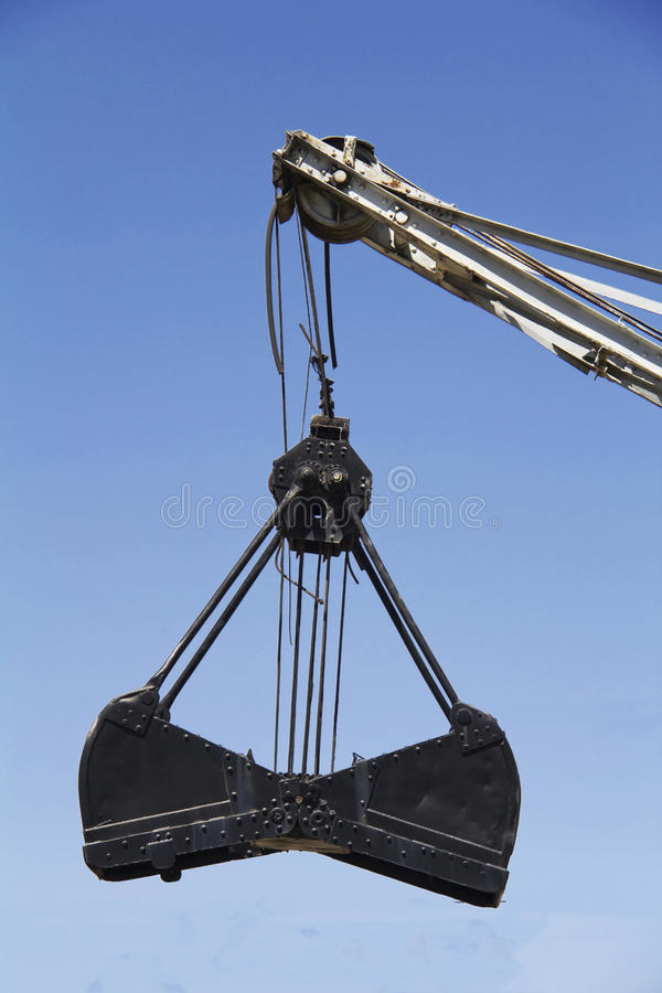 Grapple. Crane fills sand into container stock photography