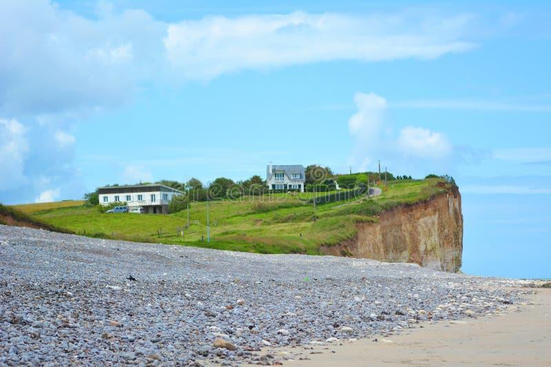 Gras behandelde klip met gebouwen bij strand bij Saint-Aubin-sur-Mer in Normandië Frankrijk royalty-vrije stock foto