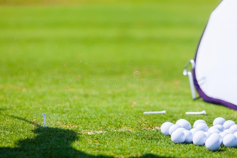 Gras-Spritzen nach dem Golf-Spieler, der Ball schlägt lizenzfreie stockbilder