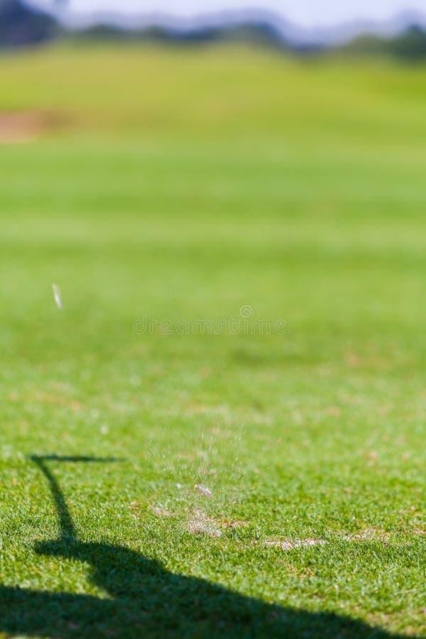 Gras-Spritzen nach dem Golf-Spieler, der Ball schlägt stockfoto