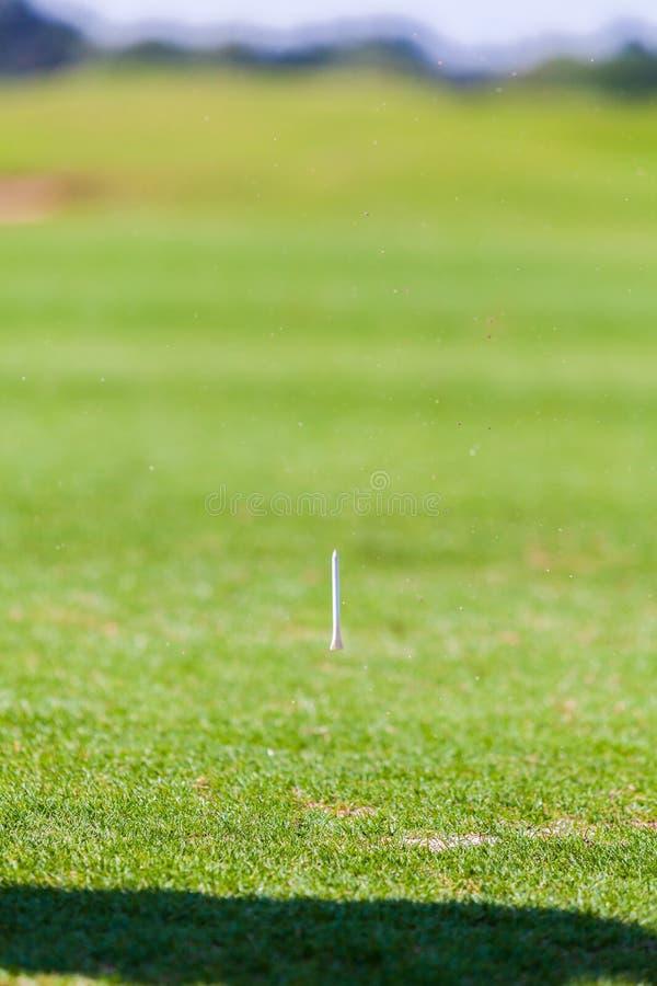 Gras und T-Stück spritzen nach dem Golf-Spieler, der Ball schlägt lizenzfreie stockbilder