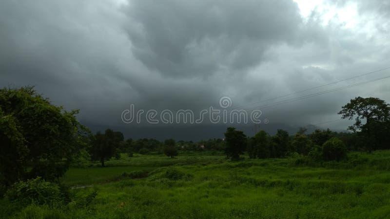 Grasartige Landschaft beschattet durch dunkles clouda stockfoto