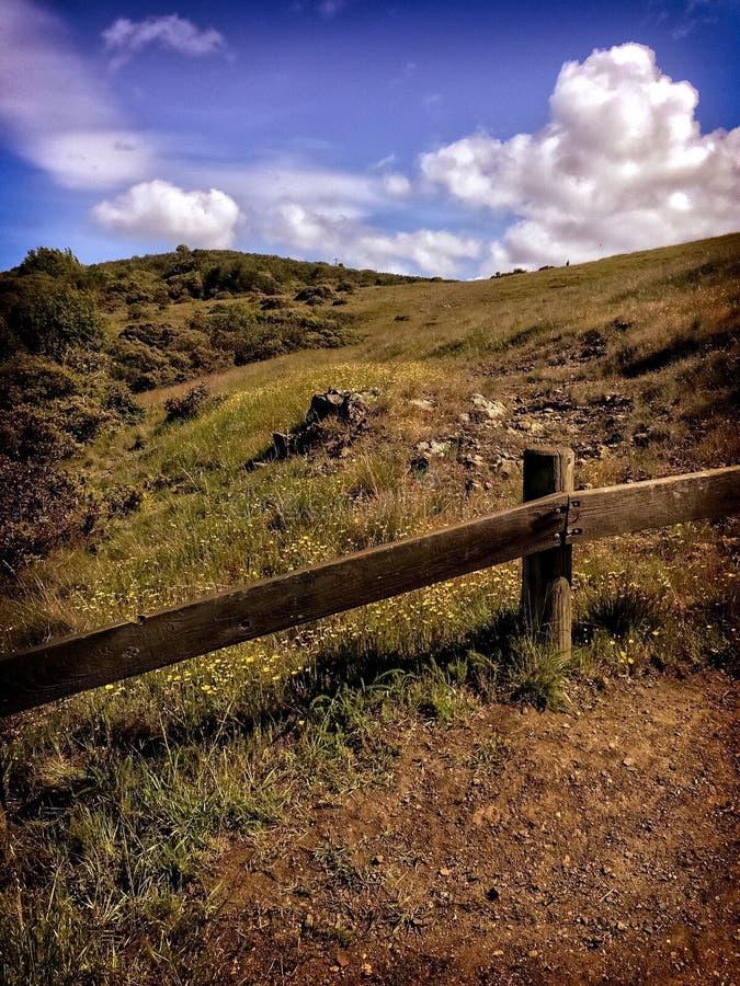 Grasartiger Hügel mit Zaun stockfotos