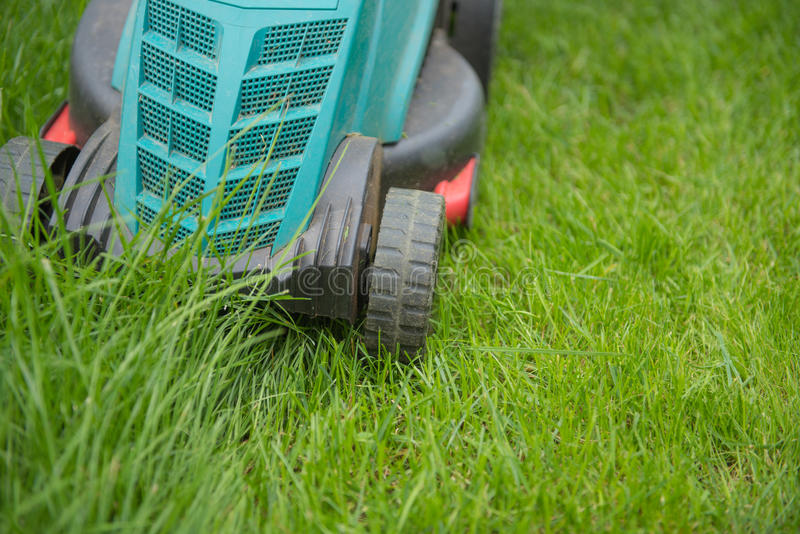 Grasmaaimachine op het groene gras, knipsel, close-up stock foto's