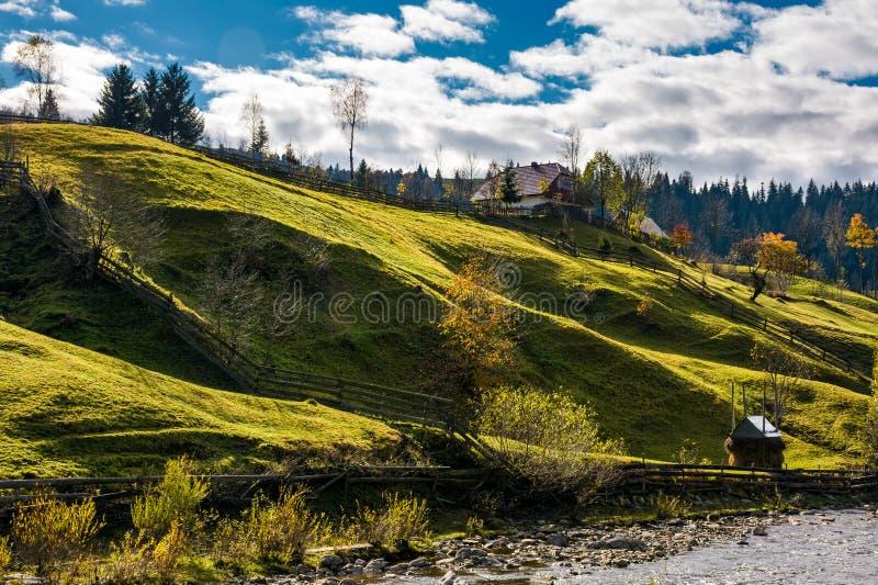 Grasrijke landelijke helling dichtbij het dorp in de herfst royalty-vrije stock afbeelding