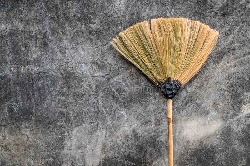 A grass broom lay against the old cement wall. Thailand royalty free stock images