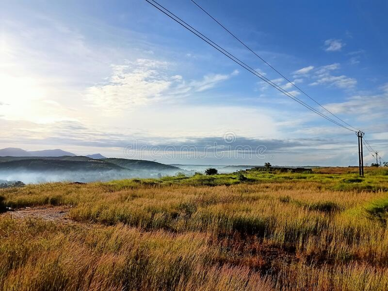 Grass and the electrical line view from the mountain top sunrise royalty free stock images