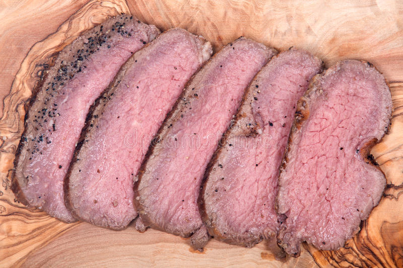 Grass fed juicy corn roast beef. On olive wood cutting board royalty free stock image