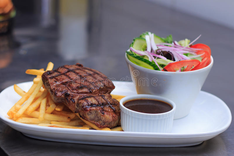 Grass Fed Rump Steak with chips salad and pepper sauce royalty free stock photography