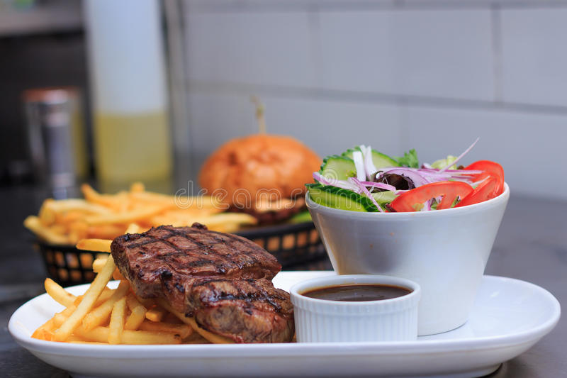 Grass Fed Rump Steak with chips salad and pepper sauce stock photo
