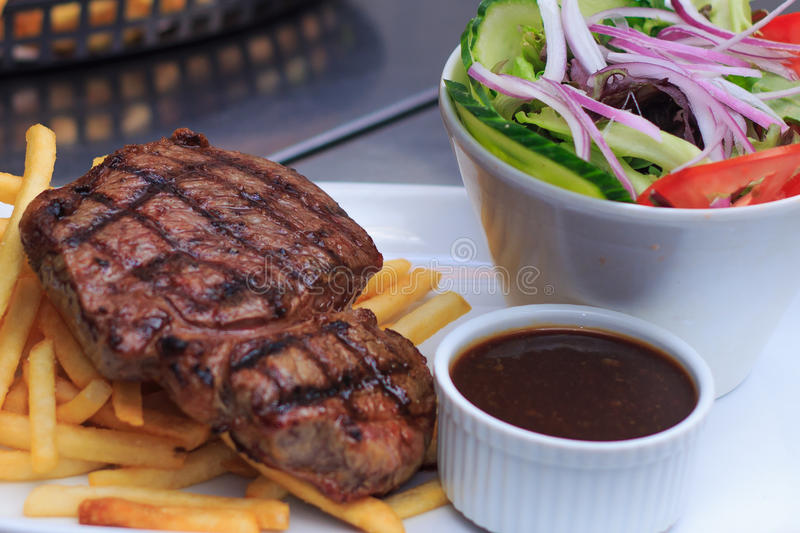 Grass Fed Rump steak 250g with chips and salad royalty free stock photography