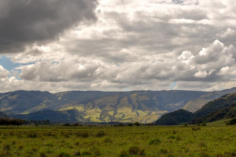 Grass field and the central Andean mountains  II. Grass field and the central Andean mountains of Colombia iin a cloudy day stock photos