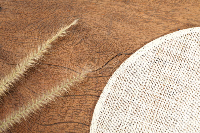 Grass flower on hard wood. Close up photo of mature grass flower putting on the dark brown color hard wood and platemat in the scene represent the detail of royalty free stock photos