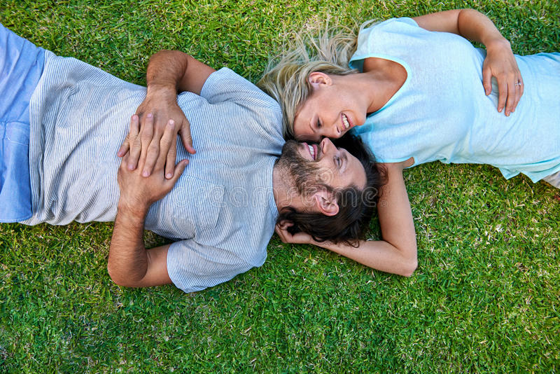 Grass laying couple royalty free stock images