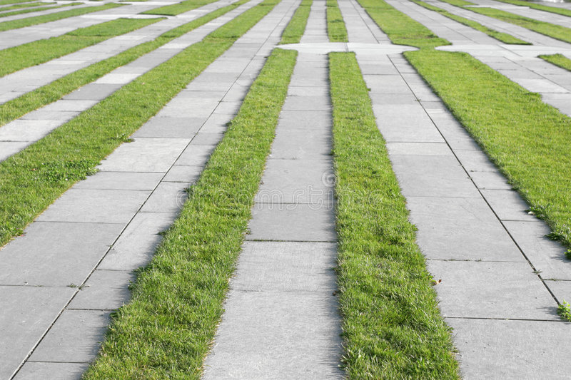 Grass pavement strips. Regular strips of mowed grass placed alternately together with sidewalk flagstones royalty free stock photo