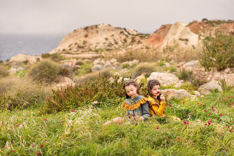 On the grass plateau sit two sisters girls in retro clothes are considered sniffing flowers with hills and stormy sea on a backgro royalty free stock photography