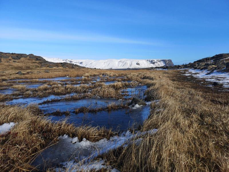 Grass, snowy mountain and ice water landscape in Iceland. Beautiful grass, snowy mountain and ice water landscape in Iceland scene under a blue sky stock photos