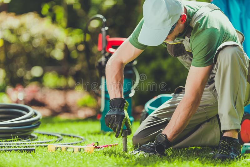 Grass Sprinklers Installation. Grass Field Sprinklers Installation by Professional Caucasian Garden Systems Installator royalty free stock images