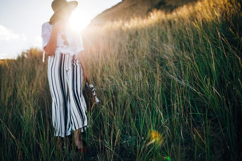 Grass in sunny evening light at sandy cliff near sea and blurred boho girl in hat posing in sun. Happy young hipster woman. Relaxing on tropical island beach royalty free stock photo