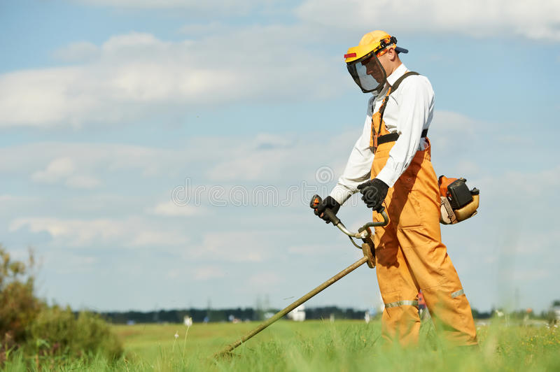 Grass trimmer works stock photos
