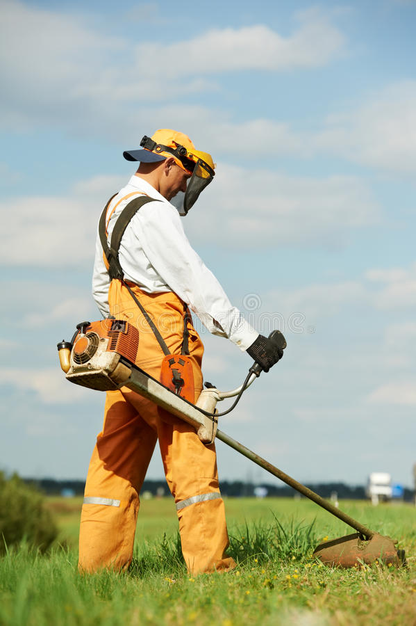 Grass trimmer works. Young worker with power tool string lawn trimmer mower cutting grass near road stock photography
