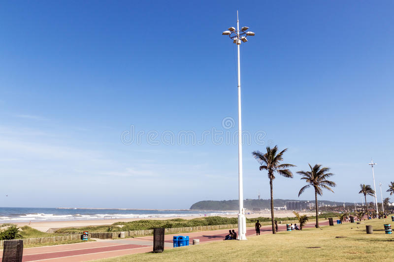Grass Verge Against Ocean and Blue Skyline. DURBAN, SOUTH AFRICA - DECEMBER 19, 2016: Early morning grass verge against Goldem Mile beach front skyline in Durban royalty free stock images