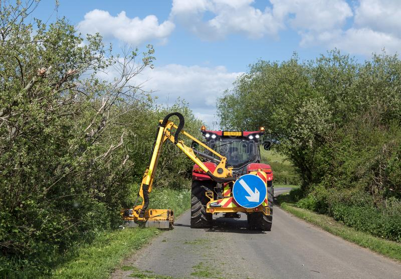 Grass Verge Cutter in Sussex. Grass verges being cut by large tractor mower in Sussex country lane during Springtime royalty free stock image