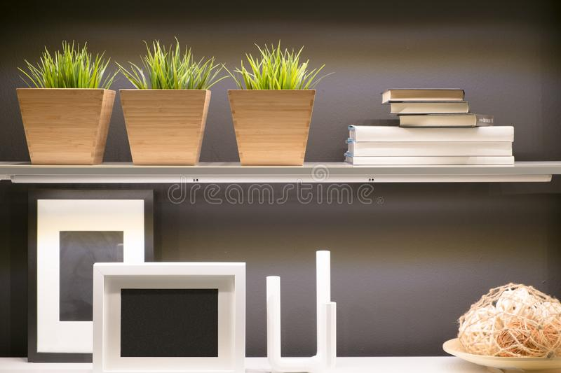 Grass wood vase, book and frame picture on home shelf. Furniture for idea concept stock photography