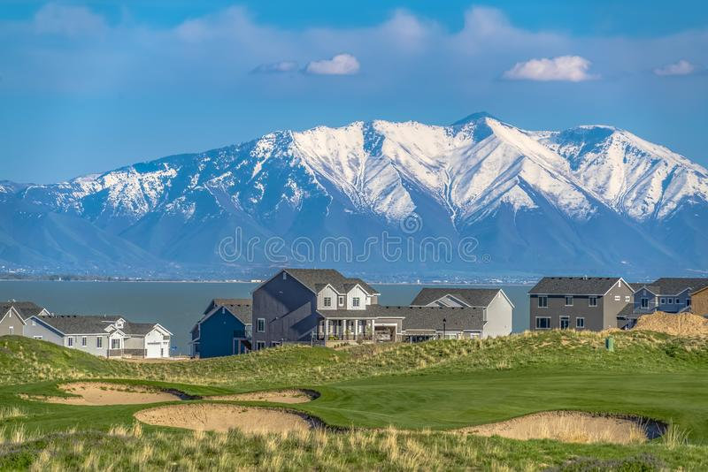 Grassy hill with houses overlooking a vast lake and snow capped mountain. Cloudy blue sky cna be seen over the valley on this sunny day royalty free stock photos
