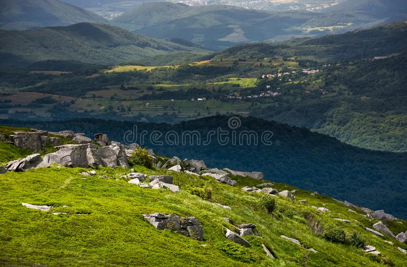 Grassy meadow with rocky formations in mountains stock images