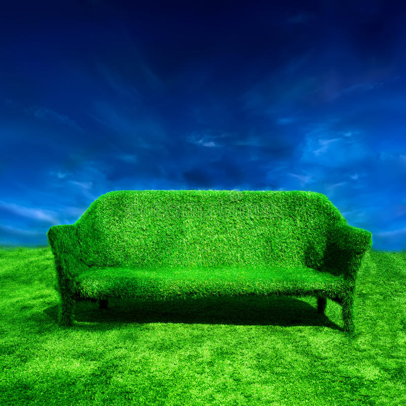 Grassy sofa standing at green grass over blue sky royalty free stock image