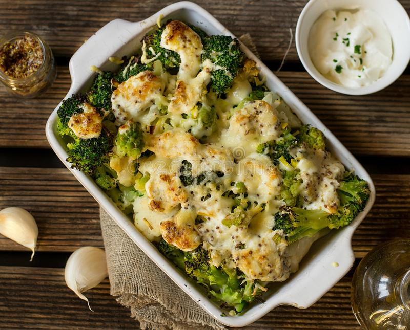 Gratén cocido de la coliflor, del bróculi y del romanesco con crema y salsa de mostaza imagen de archivo