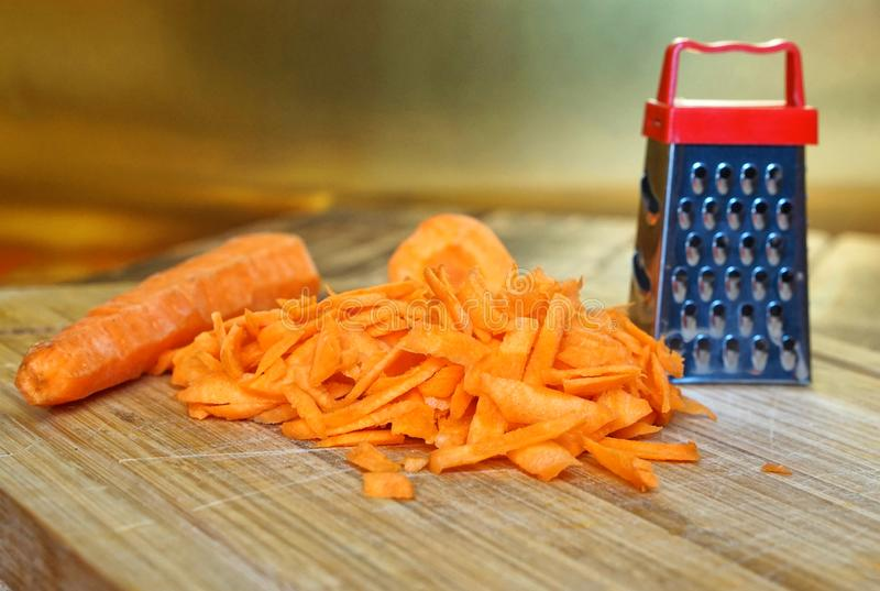 Grated carrot lies on a wooden cutting board on a golden background. Unusual mystery and optical illusion. Small and big stock photo