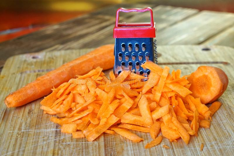Grated carrot lies on a wooden cutting board on the kitchen table. Unusual mystery and optical illusion. Small and big royalty free stock images