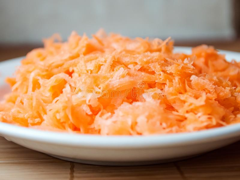 Grated carrots in bowl stock photos
