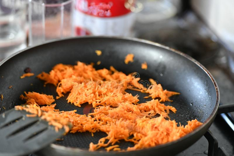 Grated carrots with onions in a skillet for frying stock photos