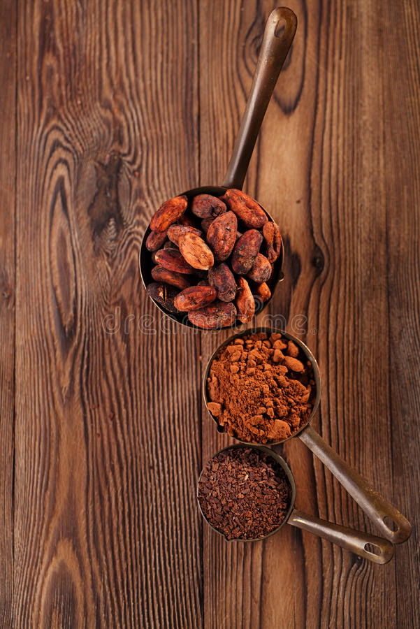 Grated chocolate, powder and cocoa beans. In vintage measuring copper pans on old wooden background royalty free stock photo