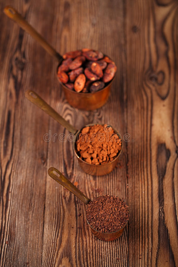 Grated chocolate, powder and cocoa beans. In vintage measuring copper pans on old wooden background stock photo