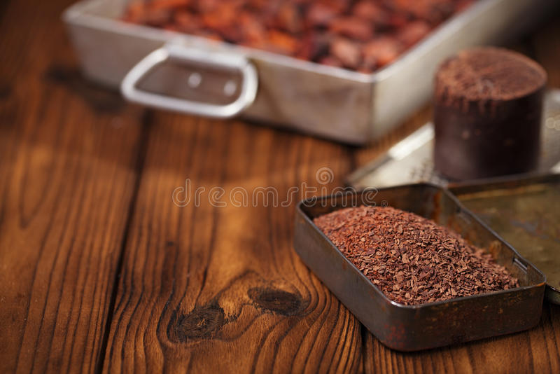 Grated dark chocolate in tin with cocoa beans and solid piece in stock images