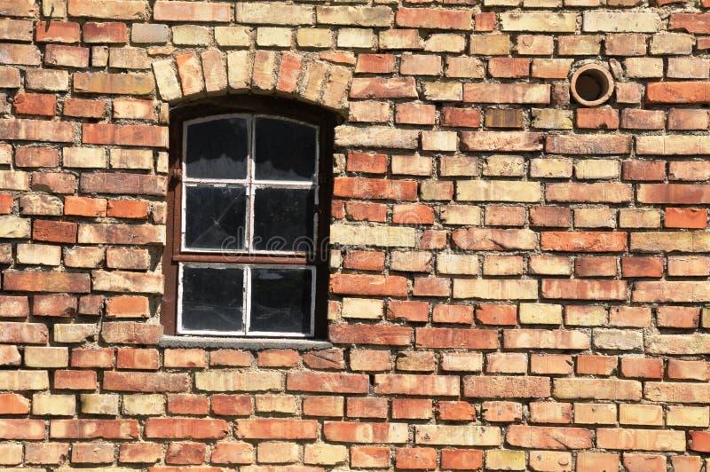 Grated fönster i vägg av tegelstenar royaltyfri bild