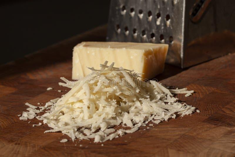 Grated italiensk parmesanost p? tr?sk?rbr?da med ett kvarter av parmasan och ett rivj?rn i bakgrunden St?ng sig upp fotoet arkivbilder