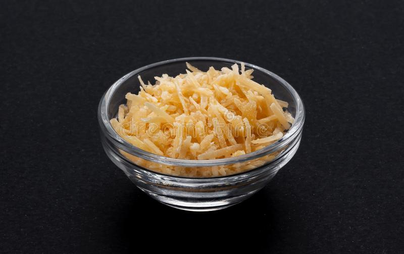 Grated parmesan cheese in glass bowl, black background stock photography