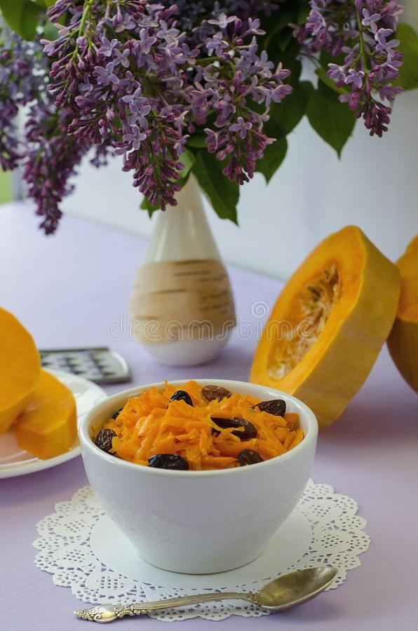 Grated pumpkin salad with raisins l on a lilac table with a bouquet of lilac flowers. Concept: raw foods, veganism, vegetarianism. Grated pumpkin salad with stock photos