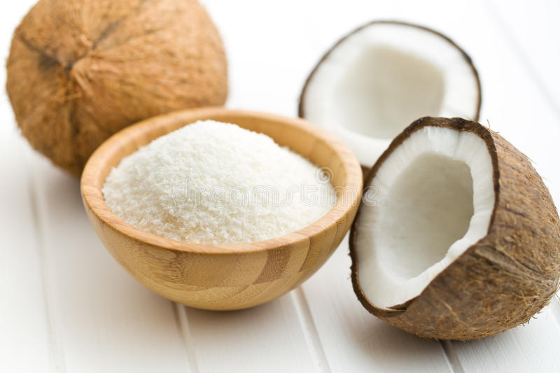 Grated, whole and halved coconut. On white table stock photos