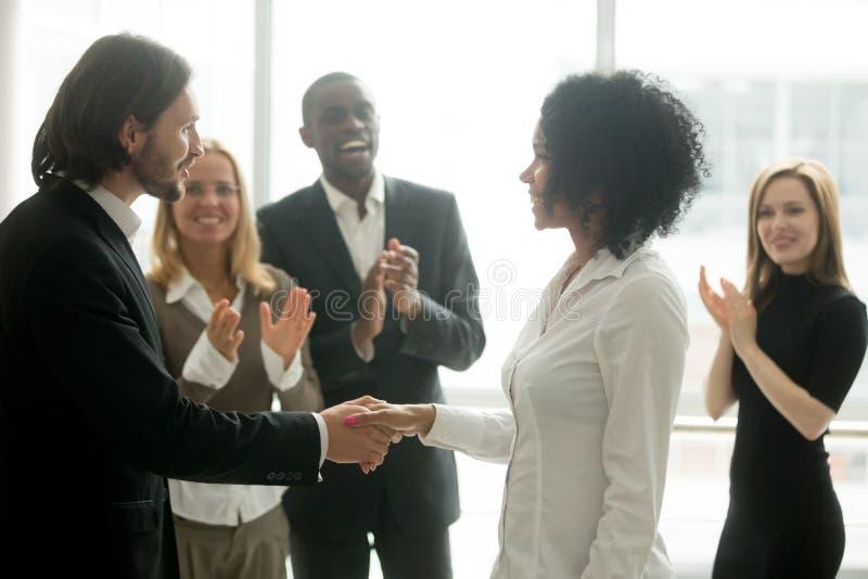 Grateful boss handshaking promoting african businesswoman congra royalty free stock images