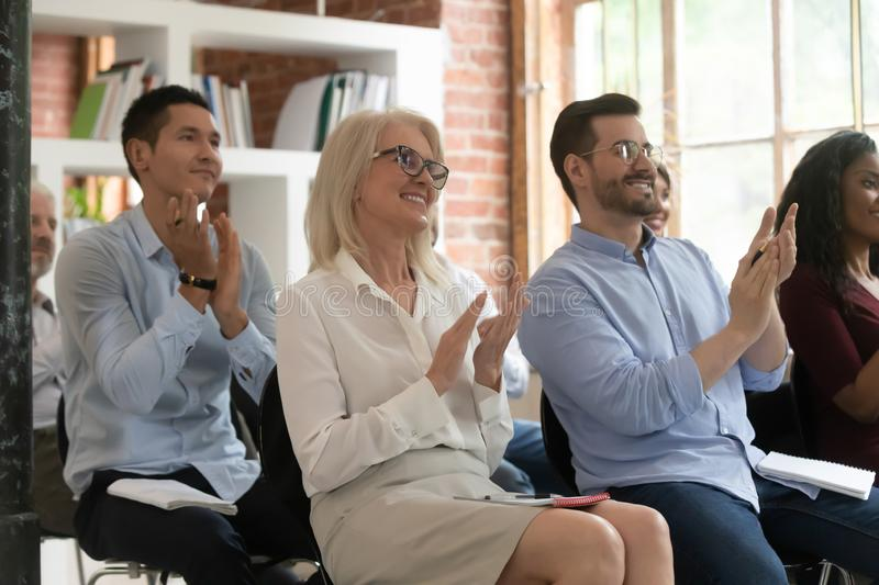 Smiling diverse coworkers applaud thanking for seminar speech. Grateful diverse employee sit at company seminar or training clap hands thanking presenter for royalty free stock photos