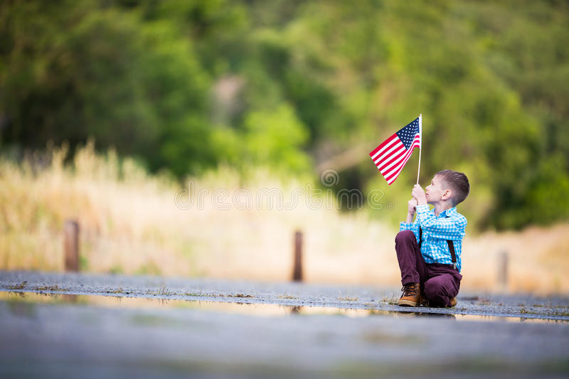Grateful for the Freedom, holding the American Flag celebrating Independence Day. A child holding the American Flag with joy for his country, United States of royalty free stock photo