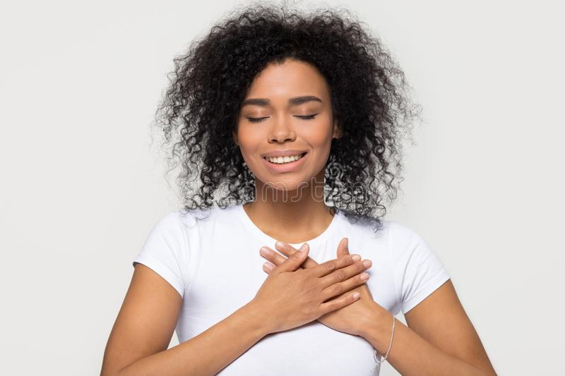 Grateful happy black woman holding hands on chest feeling thankful. Grateful hopeful happy black woman holding hands on chest feeling pleased thankful, sincere stock photos