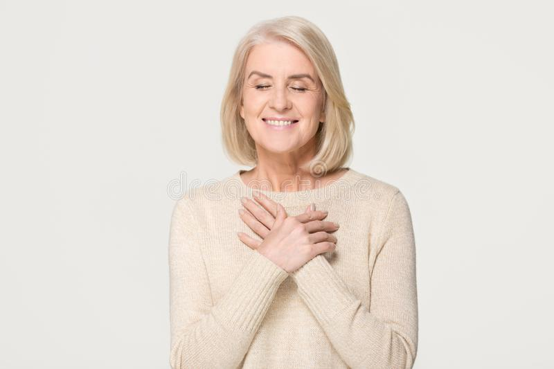 Grateful mature woman holding hands on chest isolated on background. Grateful happy mature old woman holding hands on chest feeling hopeful thanking for honesty stock image