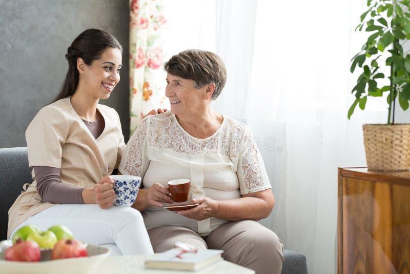 Senior lady serving tea royalty free stock photography